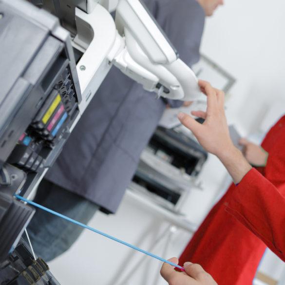 Maintenance man working on photocopier